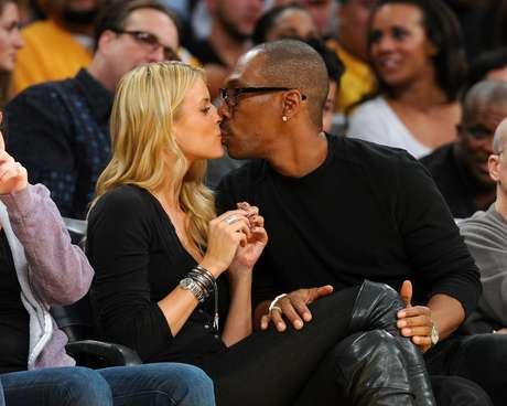 The happy couple kissed several times during the game. Not paying too much attention to the Lakers winning.