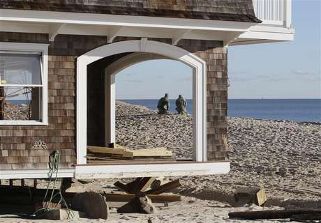 Two National Guardsmen, seen through empty window frames of a home, pause while on patrol at the beach front, to look at the ocean in the aftermath of Hurricane Sandy, at Bay Head, New Jersey November 4, 2012.