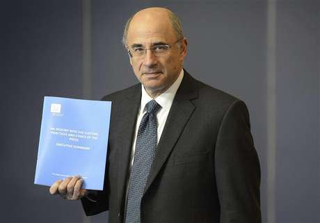 Lord Justice Brian Leveson poses with an executive summary of his report following an inquiry into media practices in central London November 29, 2012.