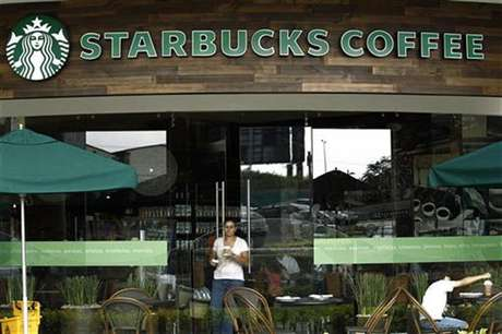 A customer with a cup of coffee leaves the new Starbucks store in San Jose June 20, 2012.