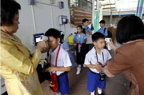 Profesoras tailandeses revisan la temperatura del cuerpo de sus estudiantes en busca de fiebre.