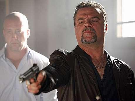 Pensando estar atirando em Morena, Russo dispara na direção de Irina Foto: Rede Globo / Divulgação