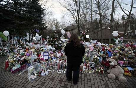 A woman stands alone at a large makeshift memorial for the victims of the December 14 shootings at Sandy Hook Elementary School in Newtown Connecticut in Sandy Hook village in Newtown early December 19, 2012. Six victims of the Newtown school shootings will be honored at funerals and remembrances on Wednesday.