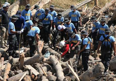 Equipes buscam por desaparecidos logo após a passagem do tufão Bopha por New Bataan, no sul das Filipinas Foto: AP