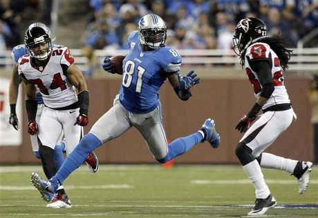 Detroit Lions wide receiver Calvin Johnson (C) carries the ball between Atlanta Falcons safety Chris Hope (L) and cornerback Dunta Robinson.