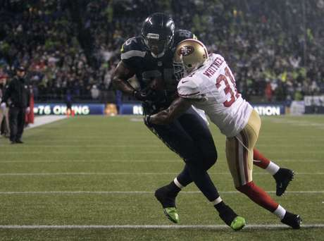 Seattle Seahawks' Anthony McCoy (L) scores a touchdown on a pass from quarterback Russell Wilson in the second quarter of their NFL football game against the San Francisco 49ers in Seattle, Washington, December 23, 2012. Defending on the play is San Francisco 49ers' Donte Whitner.