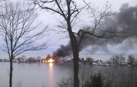 A fire burns on Lake Road after a suspect shot four firefighters responding to the blaze in Webster, New York, December 24, 2012.