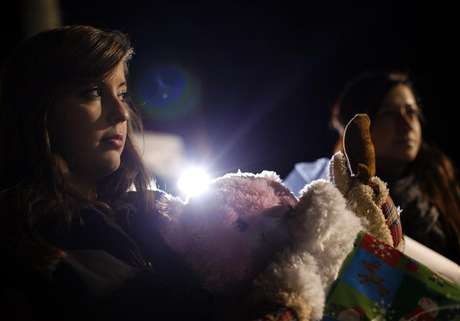 A woman holds stuff animals and Christmas presents at a memorial for the Sandy Hook Elementary School shooting victims in Newtown, Connecticut December 20, 2012.