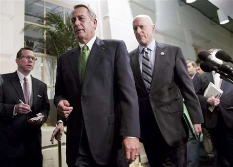 """Speaker of the House John Boehner (R-OH) (front, in green tie) walks with Congressman Dave Camp (R-MI) (R) after a meeting with House Republicans about a """"fiscal cliff"""" deal on Capitol Hill in Washington January 1, 2013."""