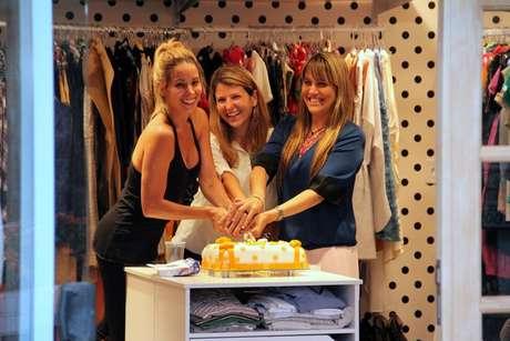 Em meio às peças de roupa, a atriz celebrou o primeiro mês de existência da sua própria loja