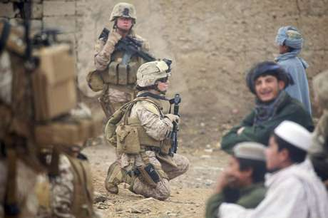 U.S. Marine Corps Lance Cpl. Sienna De Santis and U.S. Navy Petty Officer 3rd Class Heidi Dean, both with Female Engagement Team, India Company, 3rd Battalion, 5th Marine Regiment, Regimental Combat Team 2, greet children during a patrol in Sangin Valley, Afghanistan, in this October 29, 2010 DOD handout photo.