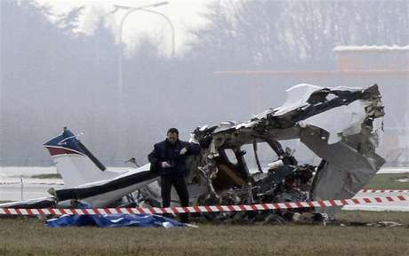 A police photographer inspects the scene of a tourist plane crash at Charleroi airport February 9, 2013. The small passenger plane crashed at Belgium's Charleroi airport on Saturday, killing five people and closing the international hub used by Ryanair and other low-cost carriers.