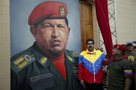 A supporter of Venezuelan President Hugo Chavez holds a copy of a photograph of Chavez released by the Ministry of Information, during a gathering at Plaza Bolivar in Caracas February 15, 2013.
