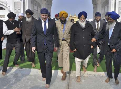 Britain's Prime Minister David Cameron (4th R) walks inside the premises of the holy Sikh shrine of Golden temple in the northern Indian city of Amritsar February 20, 2013.