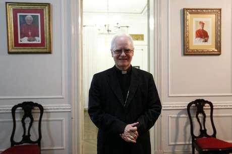 El cardenal brasileño Odilo Scherer voló esta semana a Roma para asistir al cónclave que elegirá al sucesor del Papa Benedicto XVI. Y sus fieles rezan para que no regrese. En la imagen, el arzobispo de Sao Paulo Odilo Scherer posa junto a fotografías del papa Benedicto XVI y sí mismo en Sao Paulo, el 19 de febrero de 2013.