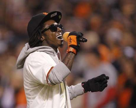 """Rapper Lil Wayne sings """"Take Me Out To The Ball Game"""" during the seventh inning stretch in Game 6 of the MLB NLCS playoff baseball series between the St. Louis Cardinals and the San Francisco Giants in San Francisco, October 21, 2012."""