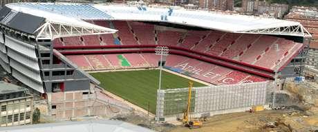 Vista del nuevo campo de San Mamés, que ya luce al completo su césped a tres semanas de su inauguración oficial, en el partido de la cuarta jornada de Liga que enfrentará al Athletic Club con el Celta el fin de semana del 14 y 15 de septiembre. Con ese rectángulo verde, los asientos rojos ya instalados y la visera cubriendo las tribunas ya levantadas, la construcción va tomando cuerpo, a pesar del hueco abierto que será finalizado según vaya avanzando la temporada. EFE/LUIS TEJIDO