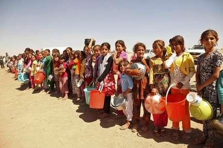 Crianças yazidi, fugidas da violência na cidade iraquiana de Sinjar, fazem fila para receber alimentos num acampamento nos arredores da província de Dohuk Foto: Ari Jalal / Reuters