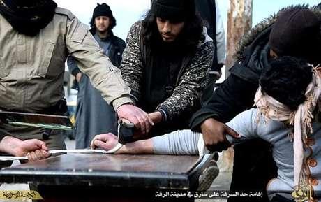 Membros do Estado Islâmico são vistos cortando a mão de um jovem em praça na Síria Foto: Daily Mail / Reprodução