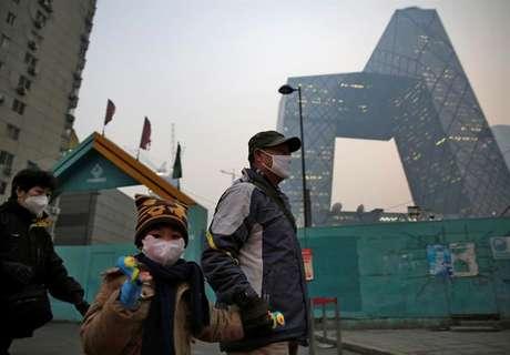 Moradores de Pequim usam máscaras devido à alta poluição do ar.