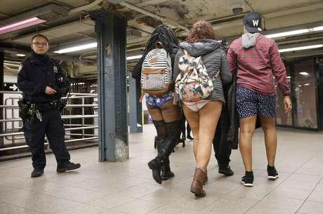 Un policía vigila una estación del metro en Manhattan mientras tres personas con ropa interior de la cintura para abajo pasan cerca durante el 15to Paseo en el Metro Sin Pantalones que se efectúa cada año en Nueva York, el domingo 10 de enero de 2016. Esta travesura que tiene el propósito de divertir se efectúa desde 2002.