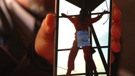 Líbio mostra no celular imagem de seu irmão, que teria sido morto a tiros e crucificado pelo EI