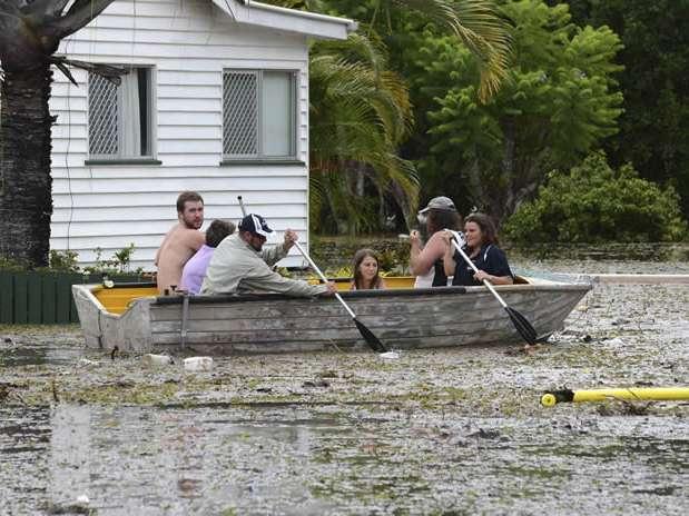 Vecinos usan un bote para abrirse paso entre el agua y los escombros que cubren una calle inundada en Bundaberg, Queensland. Foto:  / EFE en español
