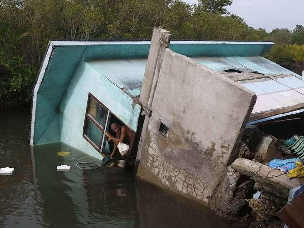 Família viu sua casa ir parar dentro de um rio após o terremoto, em Bohol Foto: Reuters