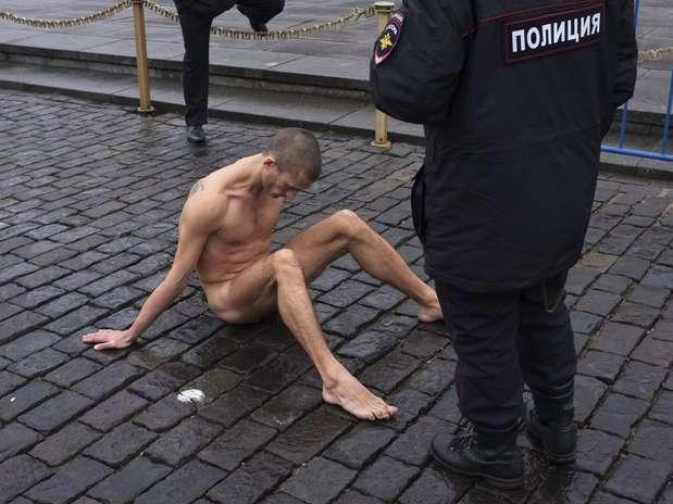 O artista russo Pyotr Pavlenski prega os próprios testículos no chão, próximo ao Kremlin, sede do governo Foto: Reuters