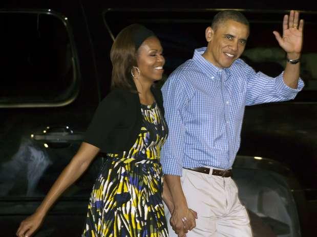 Barack Obama acena ao desembarcar de mãos dadas com Michelle em Honolulu, no Havaí Foto: AP