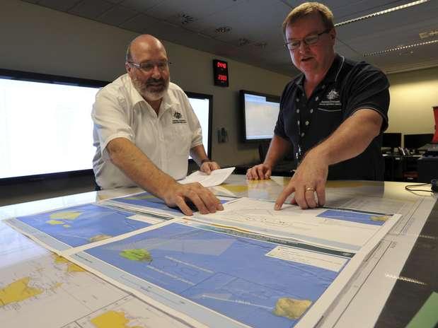Mike Barton (esq.), que comanda a equipe de resgate australiana, mostra a encarregado das operações um mapa da região em que as buscas são realizadas no Oceano Índico:26 países estão envolvidos Foto: AP