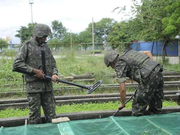 Equipes do Exército buscam armas e munições enterradas por traficantes na favela Nova Holanda, no Complexo da Maré Foto: Tomaz Silva / Agência Brasil