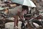 Sobrevivientes en Anibong revisan los escombros de las viviendas en busca de desaparecidos o pertenencias que puedan rescatar.