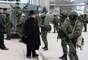 1 de março de 2014 - Civis observam militares uniformizados sem identificação que estão bloqueando base naval na Ucrânia