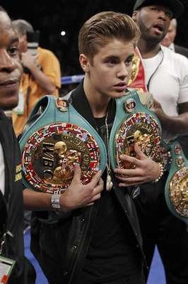 Justin Bieber carga los títulos de Floyd Mayweather Jr. previo a su pelea con Miguel Cotto en Las Vegas. (AP Photo/Eric Jamison)