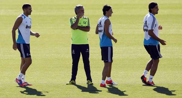 Karim Benzema (L), coach Jose Mourinho (2nd L), Mesut Ozil and Sami Khedira (R) attend a training session at Real Madrid's training grounds in Valdebebas, outside Madrid, August 16, 2012. REUTERS/Susana Vera (SPAIN - Tags: SPORT SOCCER)