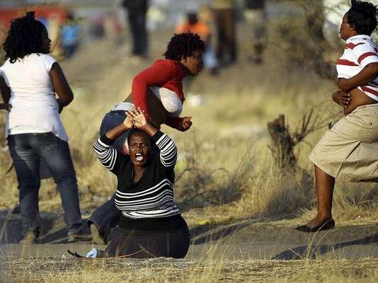 Las esposas de los 34 mineros fallecidos se manifiestan en el lugar en el que sus maridos fueron tiroteados por las fuerzas del orden sudafricanas en la mina de Lonmin Platinum de Marikana, en el centro de conferencias de la empresa minera Lonmin cerca de Rustenburg, Sudáfrica.
