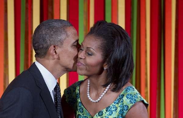"""No hacen falta paparazzis para captarlos muy cariñosos, pues los políticos de EE.UU. se demuestran el amor ante los ojos del público. Quizás, una manera de identificarse con los votantes o simplemente pura espontaneidad, pero el caso es que son muy pocos los que se escapan del lente fotográfico. En esta foto del 20 de agosto de 2012 el presidente Barack Obama besa a la Primera Dama, Michelle, antes de hablar en una cena de Estado para niños como parte de la campaña """"Muévete, vamos"""" para combartir la obesidad infantil ."""