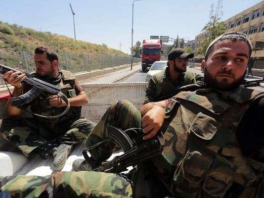 """Las tropas del régimen sirio, apoyados por artillería y aviones de guerra, lucharon en varios frentes rebeldes miércoles. El enviado especial de la ONU, Lakhdar Brahimi, calificó la cifra de muertos como """"increíble"""" y la destrucción """"catastrófica"""". En la imagen, soldados del ejército sirio viajan en la parte trasera de un vehículo militar hacia la ciudad de Sief al-Dawlah, en Alepo."""