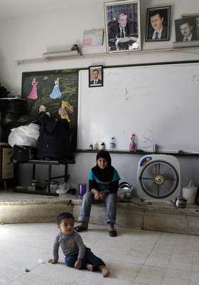 "Internally displaced children living in a classroom at a school after fleeing the violence in their hometowns due to incessant clashes between rebel fighters and government troops, pose for a picture during a tour organised by the governorate of Damascus, in the capital city of Damascus September 16, 2012. Tens of thousands of Syrians who moved into schools after air strikes and fighting drove them from their homes will be on the move again on Sunday when the government plans to start the school year despite unrelenting violence. Education Minister Hazwan al-Wazz told state television last week that around 2,000 schools have been destroyed by ""terrorists"", a term authorities use for the rebels fighting against Syria's President Bashar al-Assad."