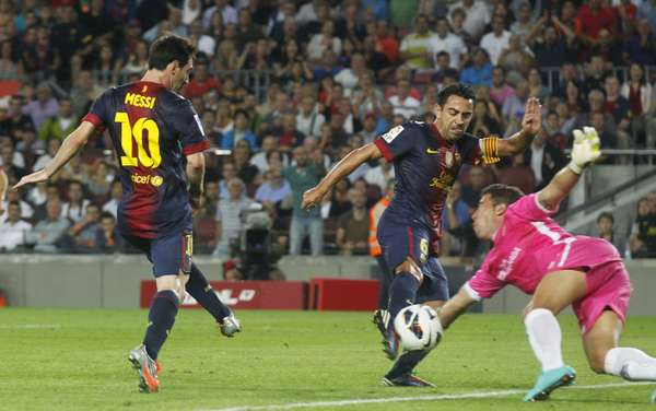 Barcelona's Xavi Hernandez (C) fights for the ball against Granada's goalkeeper Tono Martinez (R) after a Lionel Messi (L) shot during their Spanish First Division soccer league match at Camp Nou stadium in Barcelona September 22, 2012. REUTERS/Albert Gea