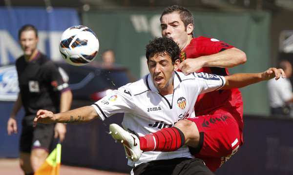 Mallorca's Antonio Lopez (R) challenges Valencia's Daniel Parejo during their Spanish First division soccer match at Iberostar stadium in Palma de Mallorca, September 23, 2012.