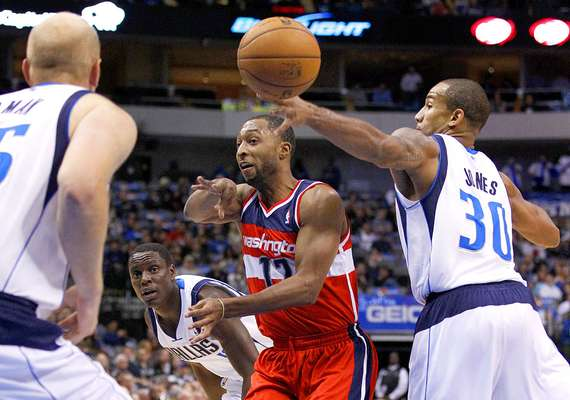 Wizards vs. Mavericks: A.J. Price (12) lanza un pase sin ver ante la marca de Chris Kaman y Dahntay Jones (30). Dallas sufrió para mantener la ventaja y vencer 107-101 ante Washington en el American Airlines Center.