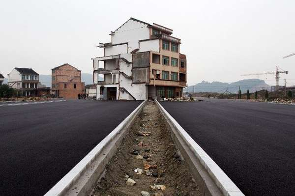 Un solitario conjunto de apartamentos erigido en medio de una moderna autopista china se presenta como reflejo inequívoco de la terquedad humana.