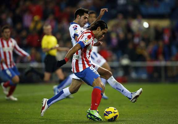 Atletico Madrid's Radamel Falcao (front) shoots past Deportivo La Coruna's Javier Camunas to score his first goal.