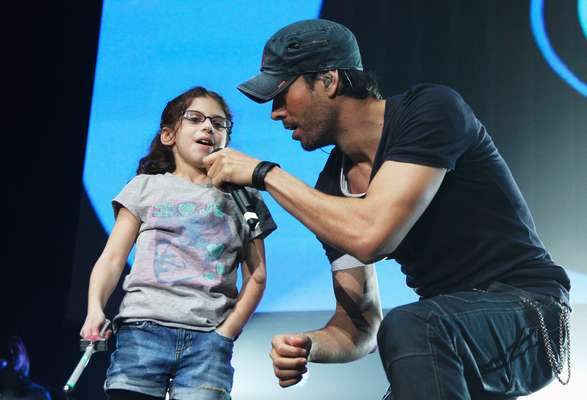 Enrique Iglesias is known for getting up close and personal with his fans at his concerts -- if they're lucky he'll land a kiss right on their lips! At last night's 'Jingle Ball' show for Atlanta radio station Power 96.1, the Spanish singer brought a special little lady on stage to sing with him during his energetic set. Take a look at Enrique being adorable with the cute kid and ruling the stage like a champion in Atlanta.