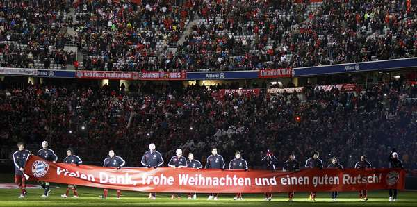 "Bayern Munich's players carry a banner that reads, ""Thank You, Merry Christmas and a Happy New Year"" after their German Bundesliga first division soccer match against Borussia Monchengladbach in Munich December 14, 2012. REUTERS/Dominic Ebenbichler"