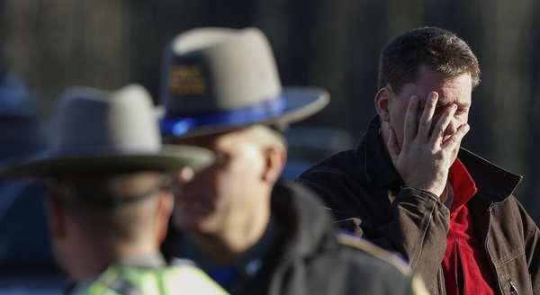 Un hombre se lamenta, delante de unos policías, por el resultado del suceso en la escuela infantil de Sandy Hook de la ciudad de Newtown en Connecticut y que se ha saldado con 26 muertos por arma de fuego , 18 de los cuales eran niños