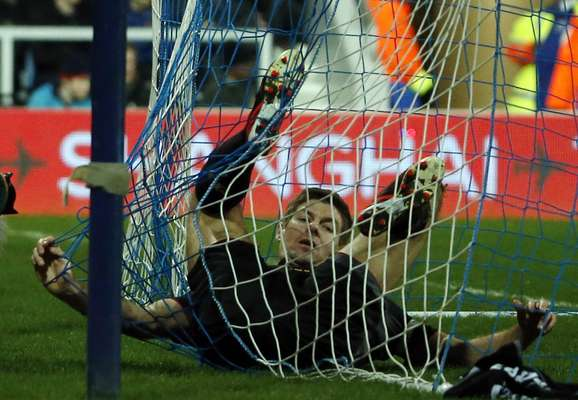 Liverpool's Steven Gerrard lies tangled in the net during their English Premier League soccer match against Queens Park Rangers at Loftus Road in London December 30, 2012. REUTERS/Eddie Keogh (