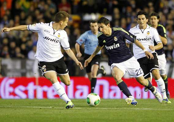Real Madrid's Angel Di Maria (C) and Valencia's Joao Pereira (L) and Tino Costa fight for the ball during their Spanish King's Cup quarter-final second leg soccer match at the Mestalla stadium in Valencia, January 23, 2013. REUTERS/Heino Kalis